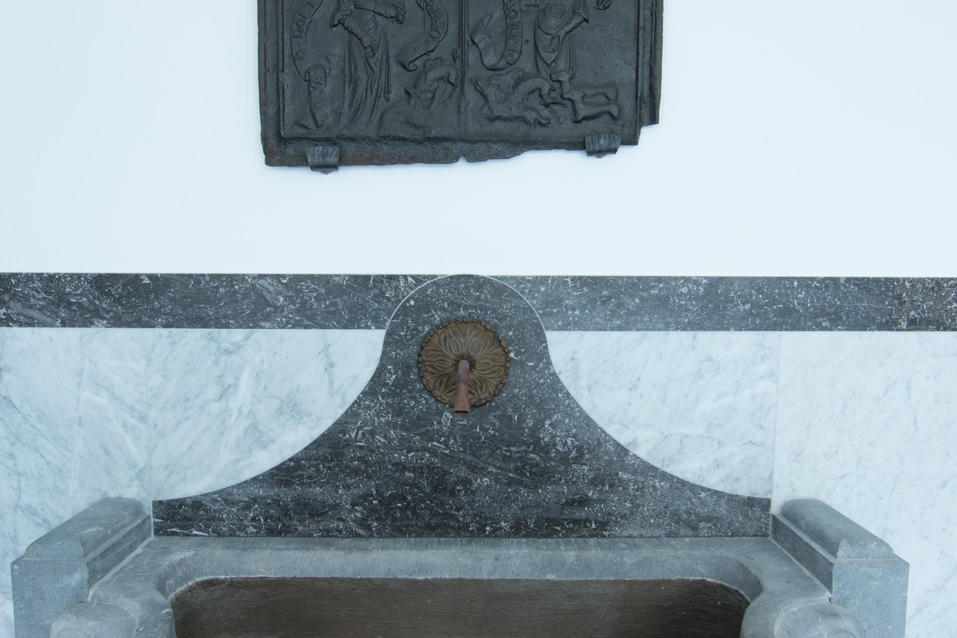 Ein alter Blausteinbrunnen wurde restauriert und in die Wand integriert.
