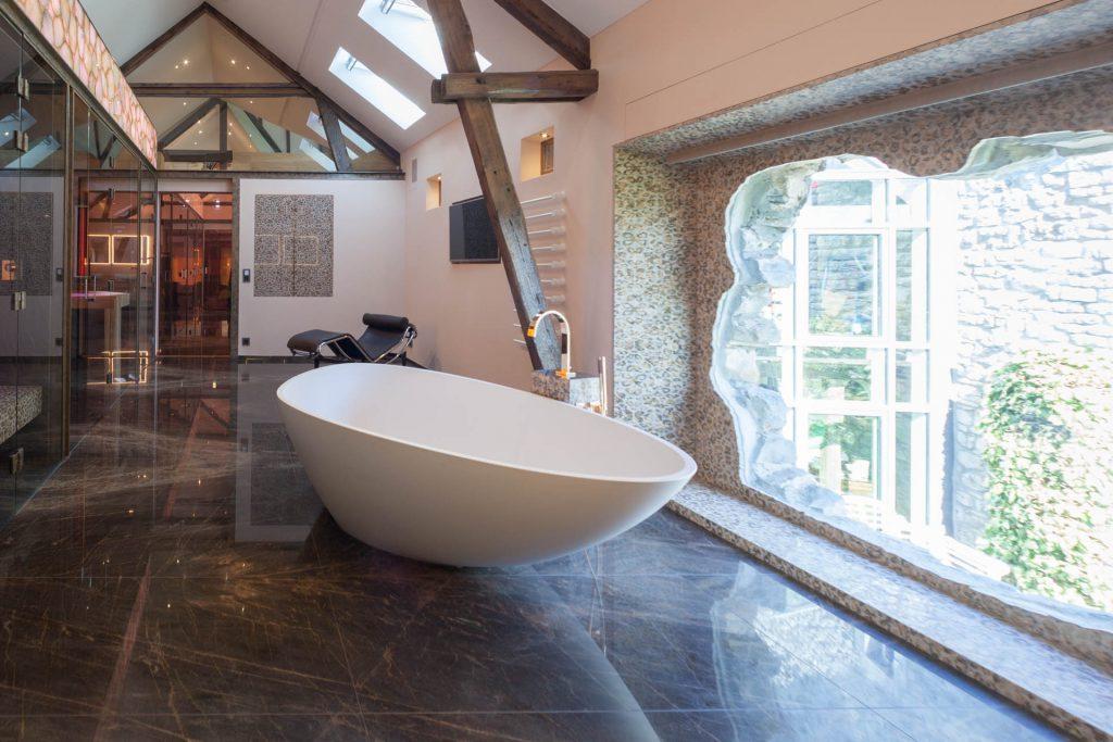 Die freistehende Badewanne bietet einen tollen Ausblick aus dem Fenster