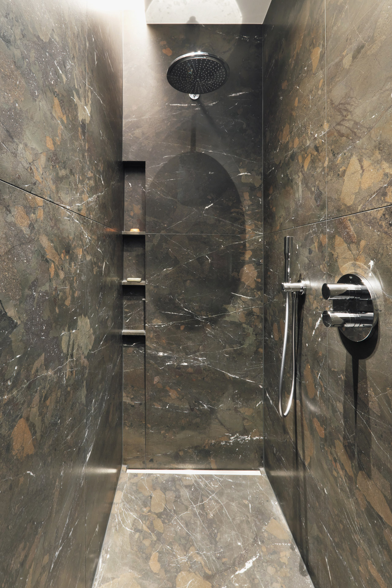 Bräunlicher Naturstein Breccia Imperiale mit feiner Maserung verbaut in der Dusche als Boden und Wandbelag