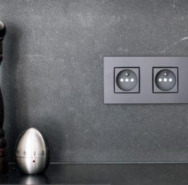 Naturstein in der Küche wie diese Küchenrückwand aus Zimbabwe Black gebürstet mit integrierten Steckdosen