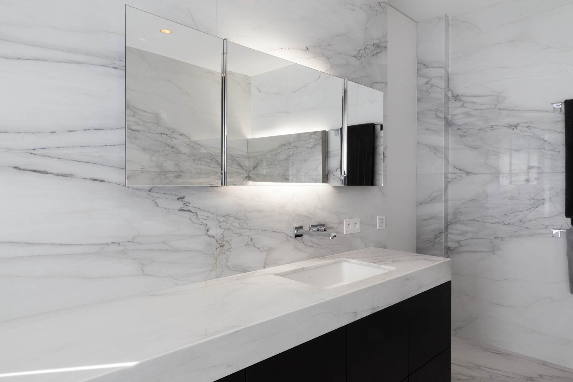 Rahmenlose Designspiegel in Kombination mit Marmorwandfliesen sind der Innbegriff modernen Baddesigns